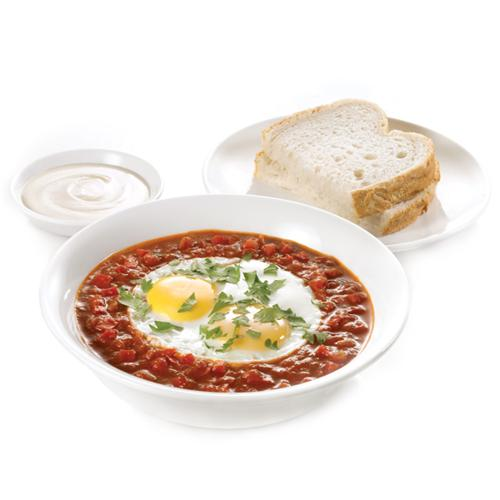 Shakshuka - A Mediterranean dish with two eggs sunny side up, tomato and peppers sauce, parsley, tahini sauce on the side and a side of bread.